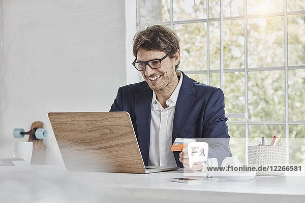 Lächelnder Geschäftsmann mit Laptop auf Schreibtisch-Haltekarte