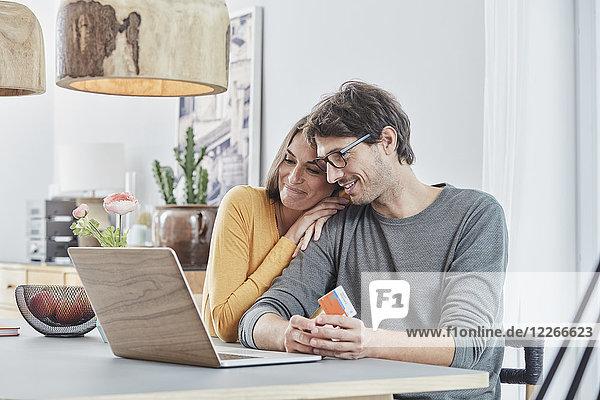 Lächelndes Paar mit einer Karte mit Laptop auf dem Tisch zu Hause