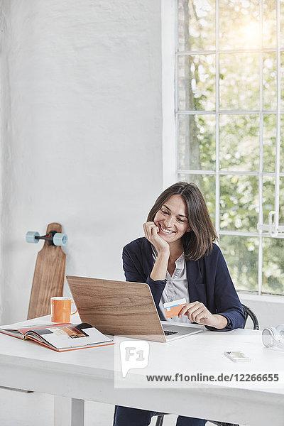 Lächelnde Geschäftsfrau mit Laptop auf Schreibtisch-Haltekarte