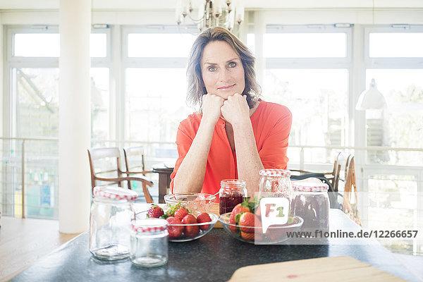Porträt einer Frau mit hausgemachter Erdbeermarmelade zu Hause