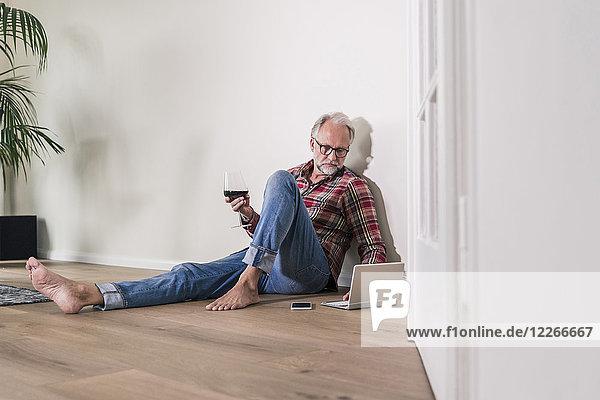 Barfußmann sitzt zu Hause auf dem Boden und entspannt sich mit Laptop und einem Glas Rotwein.