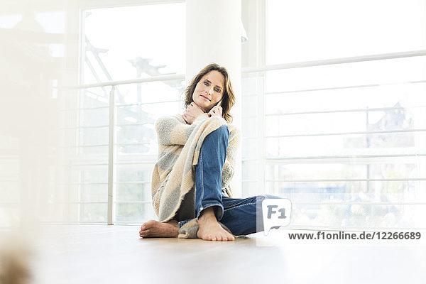 Porträt einer entspannten Frau  die zu Hause auf dem Boden sitzt.