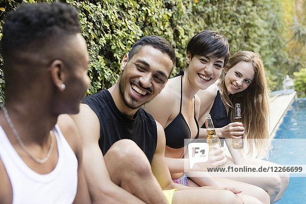 Fröhliche Freunde bei einem Bier am Pool