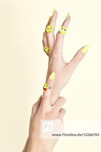 Nahaufnahme von Frauenhänden mit Emojis an Ringen