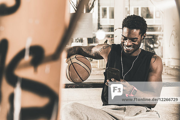 Smiling man with tattoos and basketball using smartphone and earphones