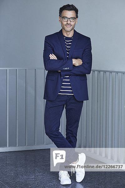 Porträt des modischen Geschäftsmannes mit blauem Anzug und Brille Porträt des modischen Geschäftsmannes mit blauem Anzug und Brille