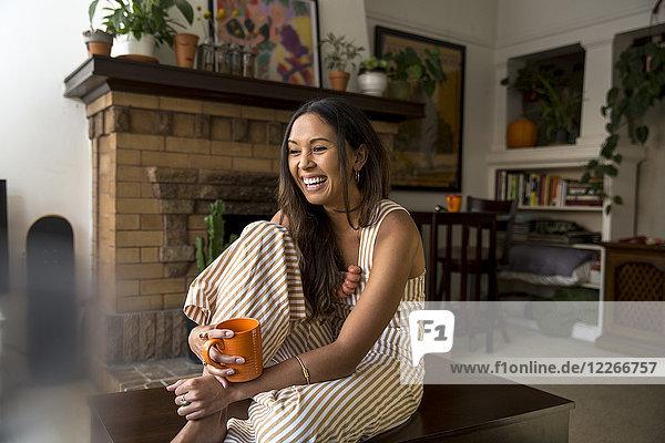 Lachende junge Frau mit Kaffeetasse zu Hause sitzend