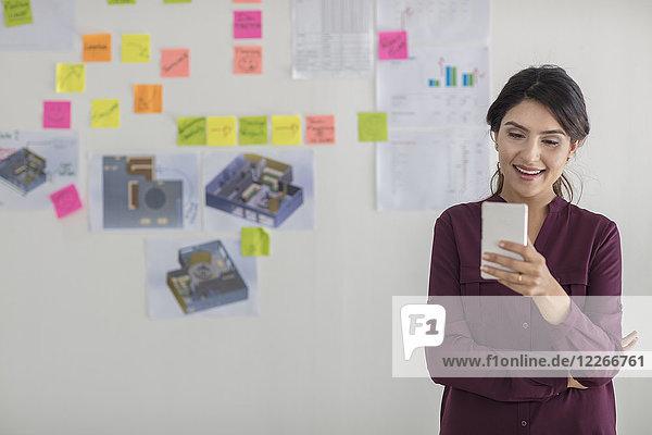 Glückliche Geschäftsfrau im Büro beim Blick aufs Handy