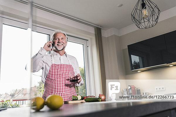Porträt eines entspannten reifen Mannes am Telefon in der Küche