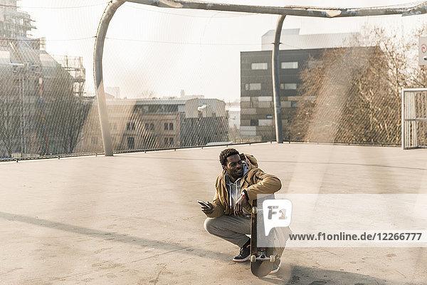 Lächelnder junger Mann mit Skateboard und Smartphone auf dem Platz