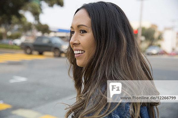 Porträt einer lächelnden jungen Frau auf der Straße