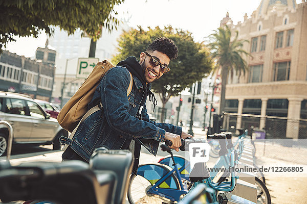 Stilvoller junger Mann auf der Straße mit Leihfahrrad