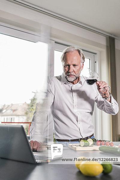 Portrait eines reifen Mannes mit einem Glas Rotwein in der Küche mit Blick auf den Laptop