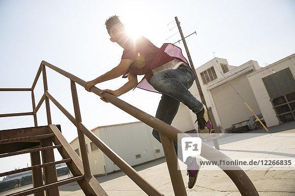 Junger Mann beim Treppenspringen im Freien