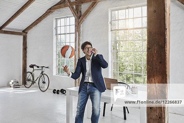 Lachender Geschäftsmann mit Basketball am Handy im Penthouse