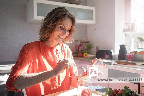 Lächelnde Frau macht Erdbeermarmelade in der Küche zu Hause