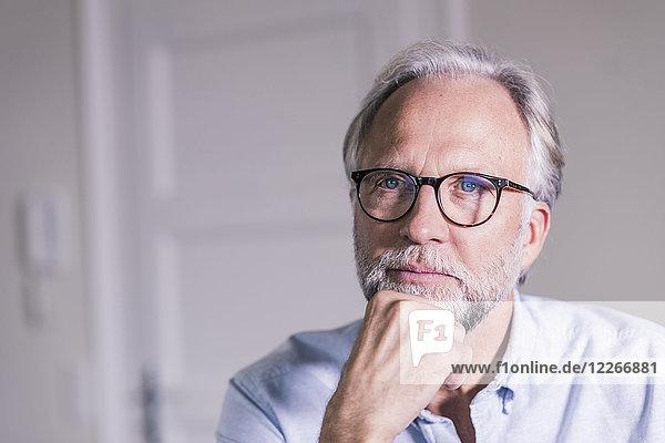 Portrait of pansive mature man wearing glasses