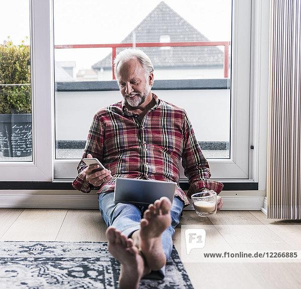 Lächelnder Mann entspannt sich zu Hause auf dem Boden mit Laptop und einer Tasse weißem Kaffee.