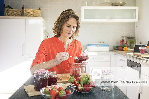 Frau macht Erdbeermarmelade in der Küche zu Hause