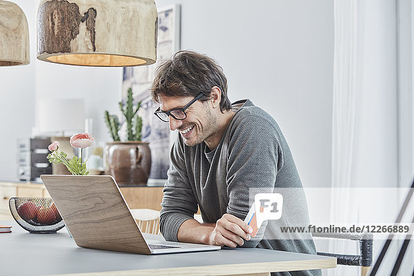 Smiling man holding a card using laptop on table at home