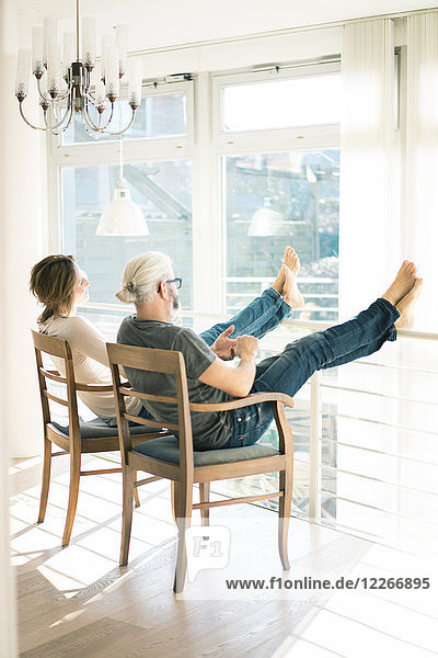 Entspanntes reifes Paar  das zu Hause auf Stühlen sitzt und die Füße hochlegt