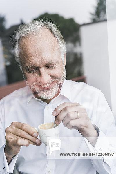 Porträt eines glücklichen reifen Mannes hinter einer Glasscheibe mit einer Tasse Espresso