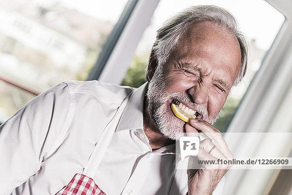 Porträt eines Mannes  der Zitronenscheibe isst