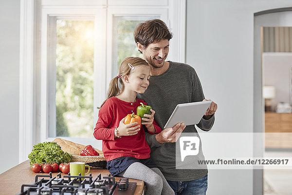 Lächelnder Vater und Tochter mit Paprika und Tablette in der Küche