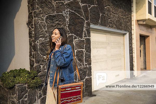 Lächelnde junge Frau spricht auf dem Smartphone auf dem Bürgersteig