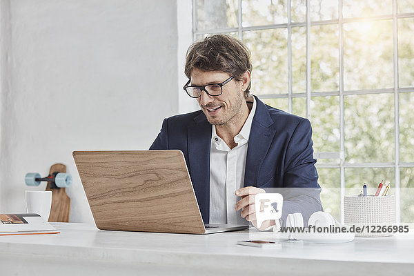 Lächelnder Geschäftsmann mit Laptop auf dem Schreibtisch