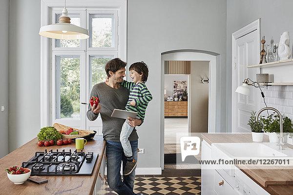 Glücklicher Vater und Sohn mit Paprika und Tablette in der Küche