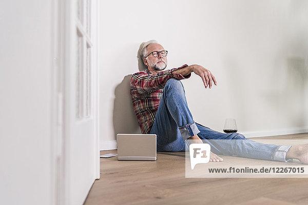 Barfuss-Mann entspannt auf dem Boden zu Hause