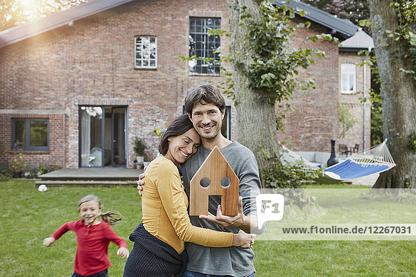 Porträt eines lächelnden Ehepaares mit Tochter im Garten ihres Hauses Modell