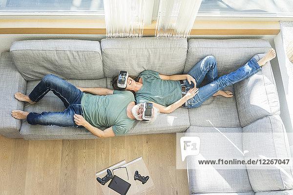 Glückliches reifes Paar  das zu Hause auf der Couch liegt und eine VR-Brille trägt.