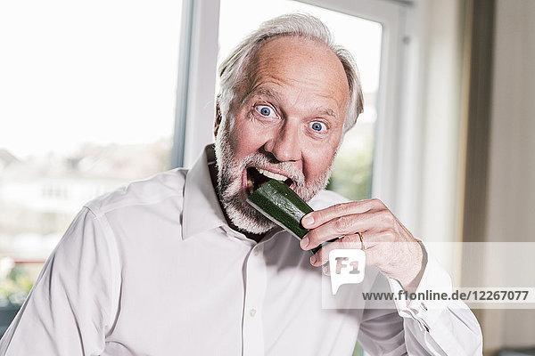Porträt eines reifen Mannes  der in Zucchini beißt