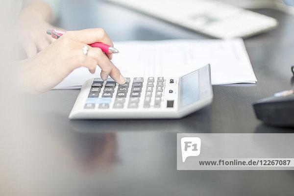 Frau am Schreibtisch im Büro mit Taschenrechner