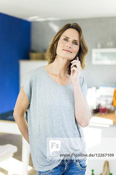 Porträt einer Frau auf dem Handy in der Küche zu Hause