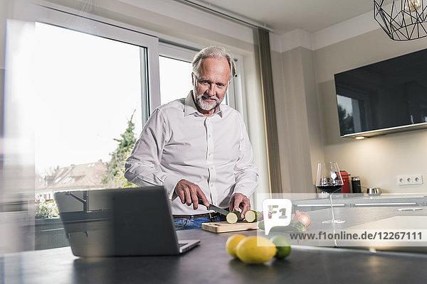 Der reife Mann bereitet das Essen in der Küche zu  während er sich den Laptop ansieht.