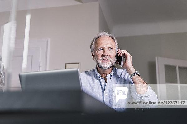 Porträt eines reifen Mannes am Telefon zu Hause