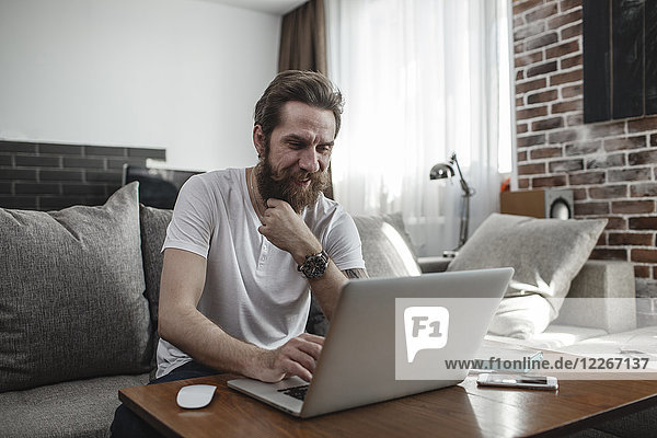 Smiling man sitting on the couch at home using laptop