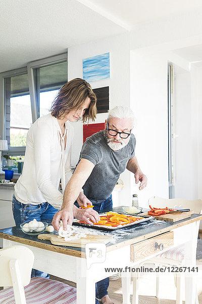 Ein reifes Paar bereitet eine Pizza in der Küche zu Hause vor.