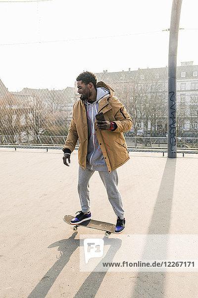Junger Mann auf dem Skateboard auf dem Platz