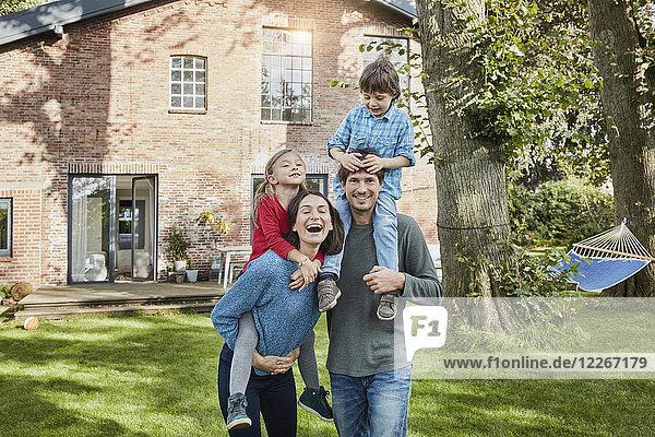 Porträt einer glücklichen Familie im Garten ihres Hauses