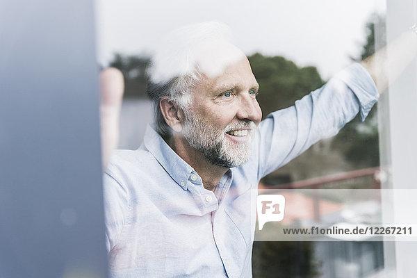 Porträt eines glücklichen  reifen Mannes  der aus der Fensterscheibe schaut.