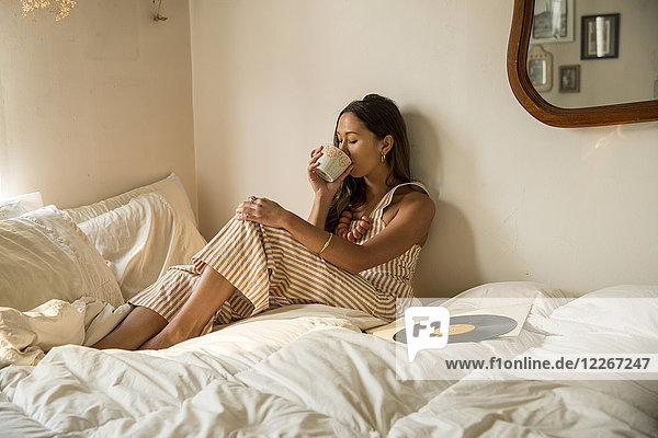 Junge Frau trinkt Kaffee aus der Tasse im Bett