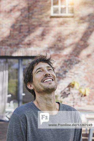 Porträt eines glücklichen Mannes vor seinem Haus