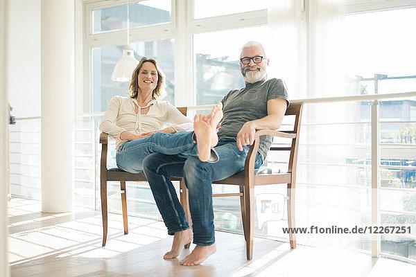 Porträt eines entspannten reifen Paares auf Stühlen zu Hause