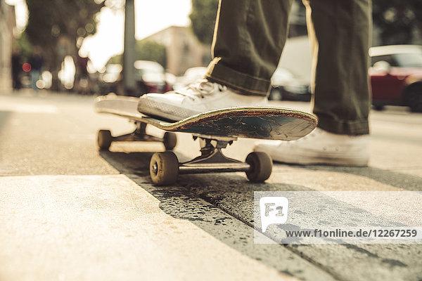 Nahaufnahme des Mannes mit Skateboard auf dem Bürgersteig