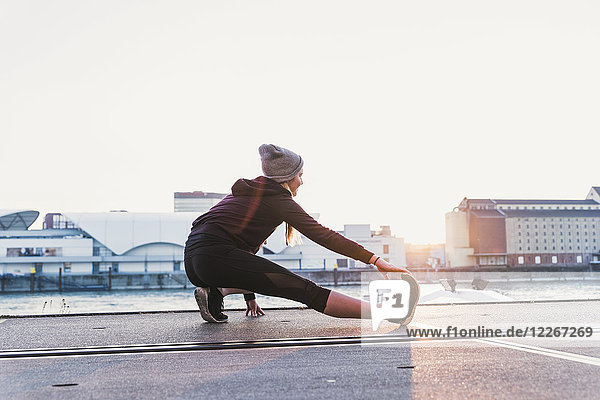 Young woman stretching at the riverside in the city at sunset