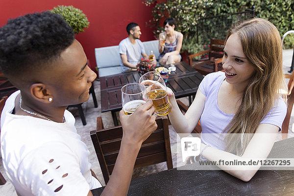 Lächelndes junges Paar bei einem Bier an der Outdoor-Bar